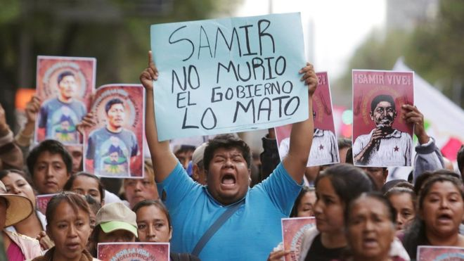 """Thousands of protesters march in Mexico City on 23 February 2019, following the murder of environmental activist Samir Flores Soberanes. A man holds a placard at the protest reading, """"Samir didn't die, the government killed him"""". Photo: Reuters"""