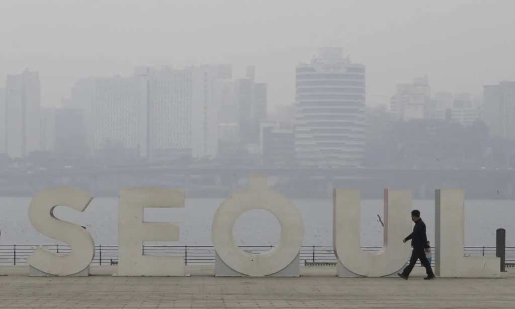 A man wearing a mask to protect from air pollution walks along the Han river at a park in Seoul on 12 March 2019. Photo: Lee Jin-man / AP