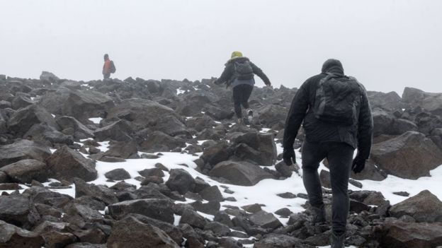 Dominic Boyer, Cymene Howe, and their student Magnus Sigurdsson climb into the mountains in August 2019 to drill holes for the Okjokull glacier memorial plaque. Photo: Josh Okun / BBC News