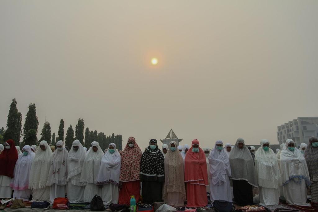 Indonesian Muslim women pray for rain during a long drought season and haze in Pekanbaru, Riau province, Indonesia, 11 September 2019. Photo: Rony Muharrman Antara Foto / REUTERS