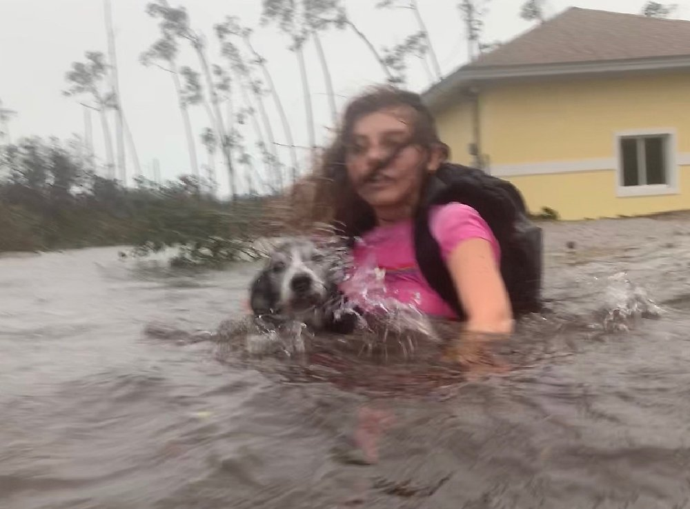 Julia Aylen wades through waist deep water carrying her pet dog as she is rescued from her flooded home during Hurricane Dorian in Freeport, Bahamas, Tuesday, 3 September 2019. Practically parking over the Bahamas for a day and a half, Dorian pounded away at the islands Tuesday in a watery onslaught that devastated thousands of homes, trapped people in attics and crippled hospitals. Photo: Tim Aylen / AP Photo