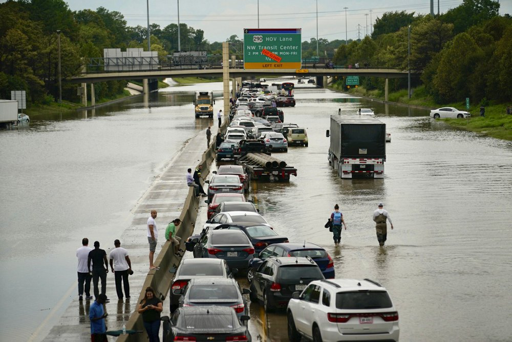 People wait outside of their stranded vehicles along Interstate 10 westbound at T.C. Jester, Thursday, 19 September 2019. The freeway is closed because of high water eastbound on the freeway from Tropical Storm Imelda. Photo: Mark Mulligan / Houston Chronicle / AP
