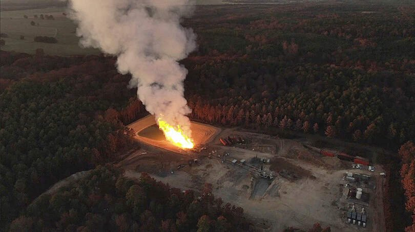 Screenshot from drone video of a fracked gas well blowout at wells operated by GEP Haynesville, LLC, in Red River Parish, Louisiana, on 1 October 2019. According to Patrick Courreges with LDNR, the well heads have been initially capped and the flow redirected through piping to flare pits to contain the produced water and keep the heat away from the wellheads where workers are trying to kill the wells at surface. Photo: Phin Percy Jr.