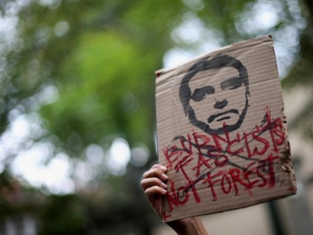 "An activist holds a sign with an illustration of Brazilian President Jair Bolsonaro that reads, ""Burn fascists, not forests"", as they demand more Amazon rainforest protection at the embassy of Brazil in Mexico City, Mexico 23 August 2019. Photo: Reuters"