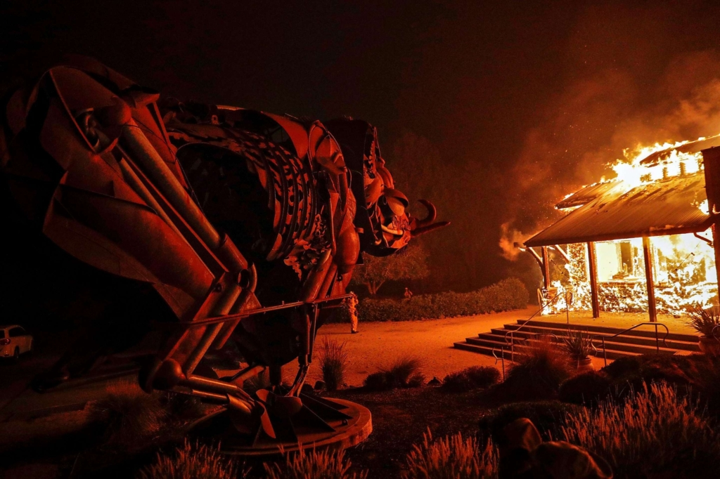 A house burns in the Kincade Fire on 23 October 2019 as a metal sculpture of an animal looks on. Photo: Carlos Avila Gonzalez / SF Chronicle