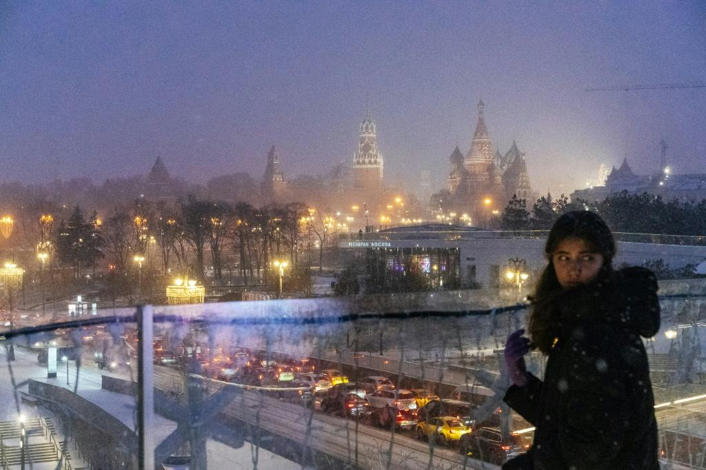 A girl overlooks a light dusting of snow in Moscow, 30 December 2019. Known for its cold winters, Moscow saw its warmest December in a century in 2019. Photo: Dimitar Dilkoff / AFP