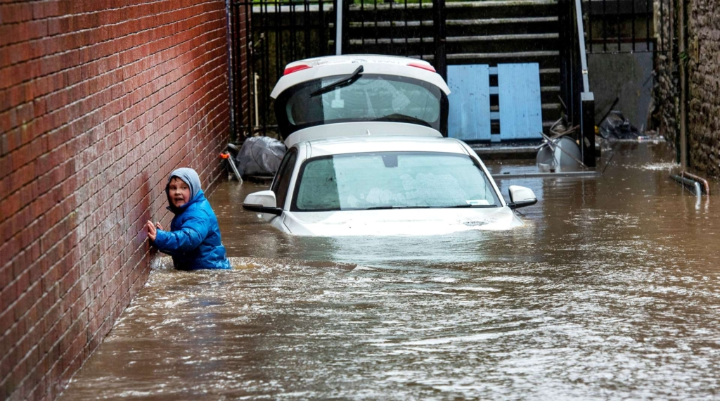 A boy wades through a flooded alleyway in Pontypridd, South Wales, on 16 February 2020. Photo: Neil Munns / EPA-EFE / Shutterstock