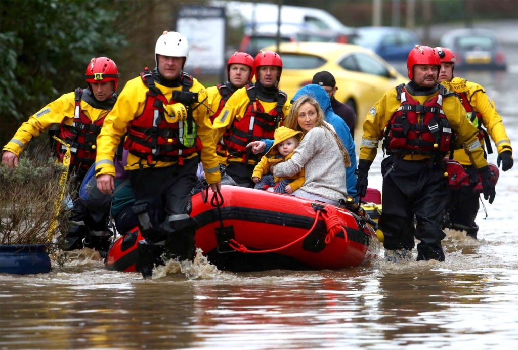 Members of emergency services evacuate residents from flooded houses by rescue boat in South Wales, on 16 February 2020. Photo: Geoff Caddick / AFP / Getty Images