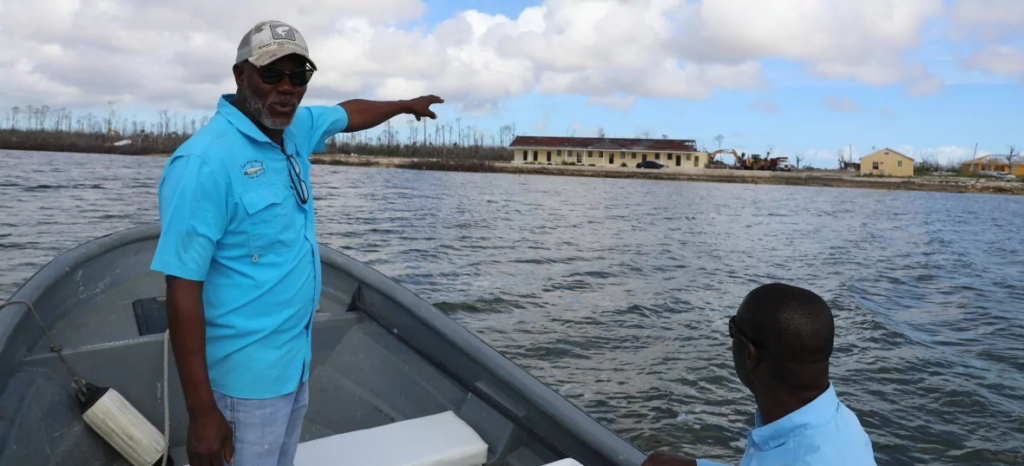 In February 2020, six months after the storm, Phil Thomas, left, points to a local school that was badly damaged by Hurricane Dorian. Photo: David Common / CBC