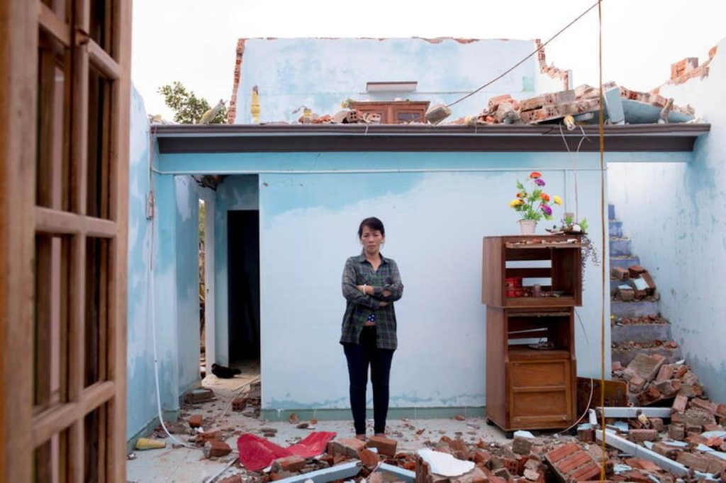 Typhoon Molave victim To Thi Cam, 51, stands in the ruins of her house in Quang Nam province, Vietnam, on 3 November 2020. Yen Duong / International Federation of the Red Cross (IFRC) / REUTERS