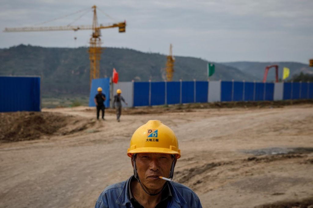 A worker stands outside a construction site of the Xinzhuang coal mine that is part of Huaneng Group's integrated coal power project, on 30 September 2020. Photo: Thomas Peter / Reuters