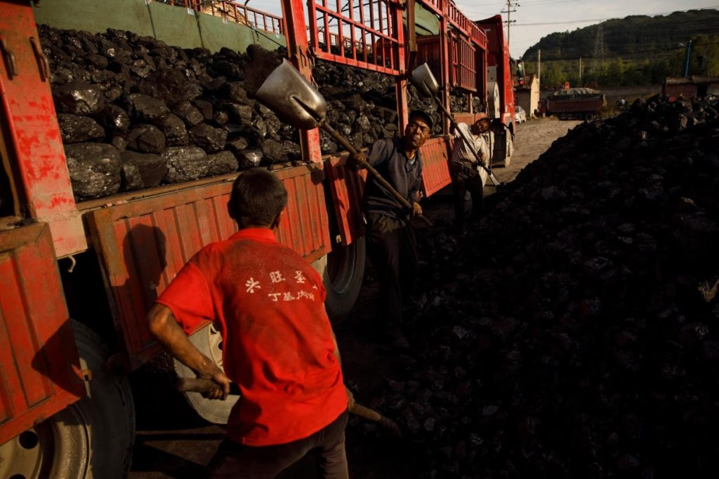 Workers shovel coal onto a truck in Huating, China, on 18 September 2020. Photo: Thomas Peter / Reuters