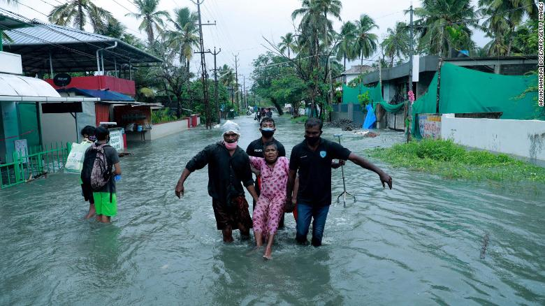 Police and rescue personnel evacuate a local resident through a street flooded by Cyclone Tauktae in a coastal area in Kochi, India on 14 May 2021. Photo: Arunchandra Bose / AFP / Getty Images