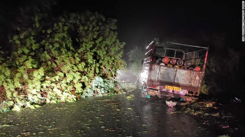 A truck loaded with oxygen cylinders is blocked by trees felled by Cyclone Tauktae, near Mahuva in Gujarat state, India, on 17 May 2021. Photo: Sam Panthaky / AFP / Getty Images