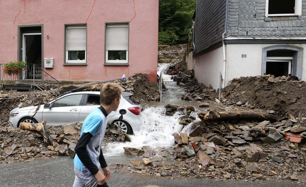A boy walks by a car in Hagen, Germany, on 15 July 2021, that was buried in debris brought by the flooding of the 'Nahma' river the night before. At least 42 people died after record rainfall caused heavy flooding and turned streams and streets into raging torrents, sweeping away cars and causing some buildings to collapse. Photo: Martin Meissner / AP Photo